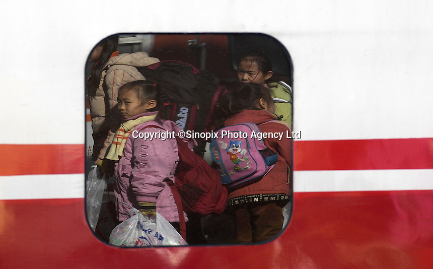 Young train communters depart Beijing during the Chinese New Year holidays at the Beijing station, China..20-JAN-04