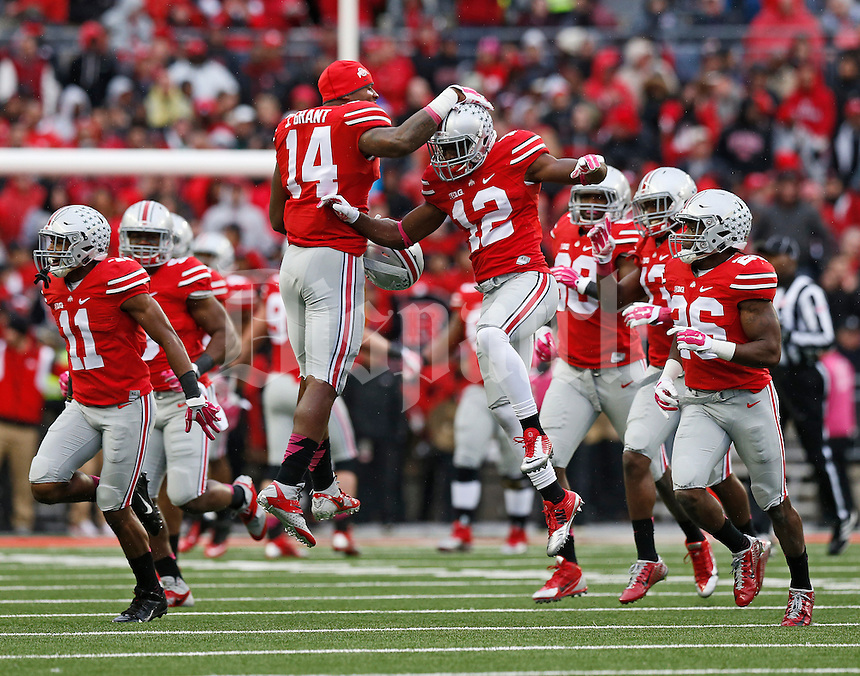 Ohio State Buckeyes linebacker Curtis Grant (14) congratulates cornerback Doran Grant (12) for making an interception during the second quarter of the NCAA football game against the Rutgers Scarlet Knights at Ohio Stadium in Columbus on Oct. 18, 2014. (Adam Cairns / The Columbus Dispatch)