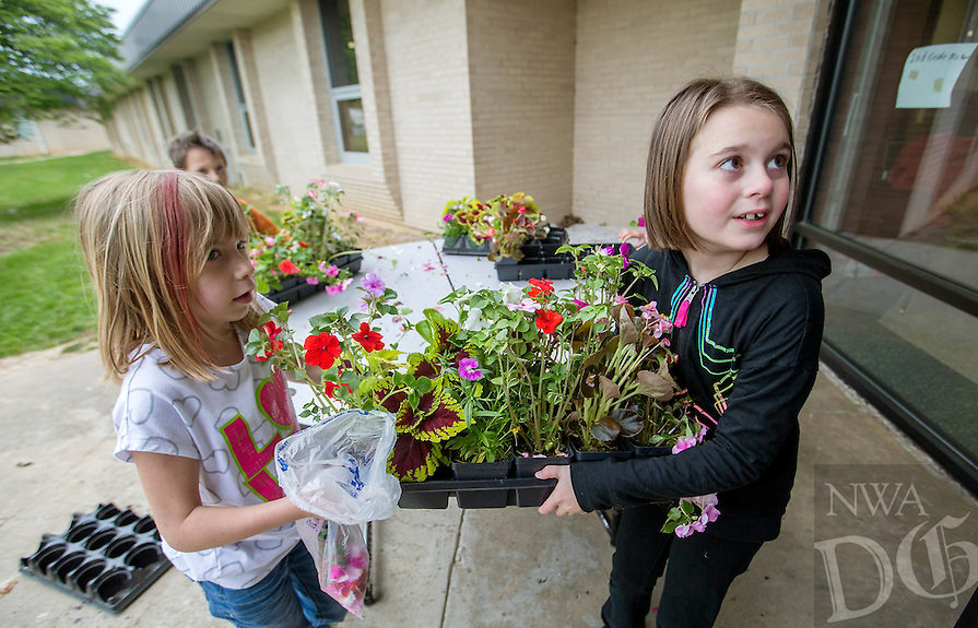 NWA Democrat-Gazette/JASON IVESTER --04/28/2015--<br /> Hannah Nichols (left) and Romy (cq) Elliott, both Eastside Elementary second-graders, carry a tray of plants on Tuesday, April 28, at the Rogers school. Second-graders at the school are selling plants for the 11th annual Mother's Day Plant Sale through Thursday. The students plant and care for the plants and then advertise and execute the sale which raises funds for the school.