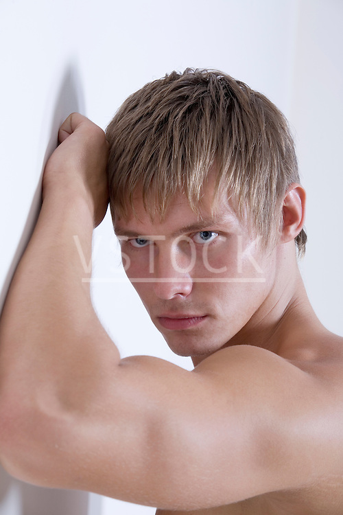 Shirtless young man leaning against wall