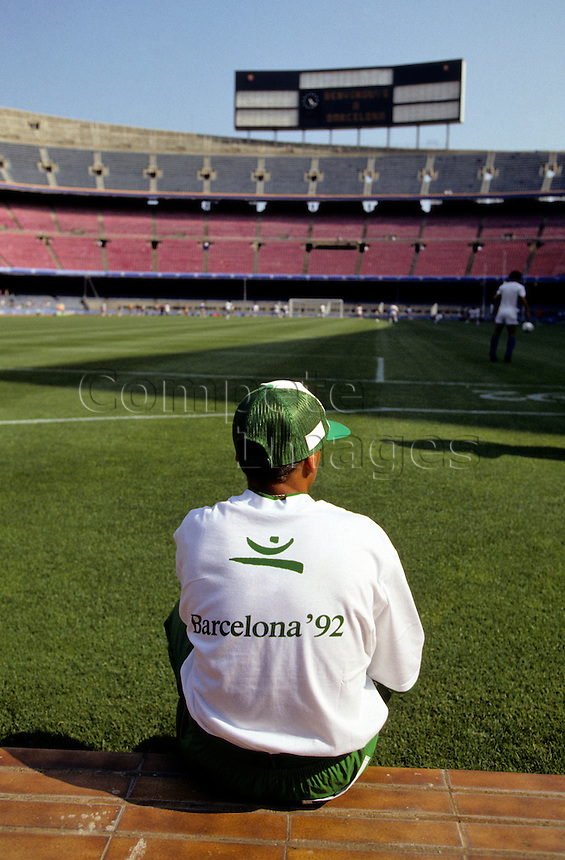 Spectator watches football player practice in a stadium