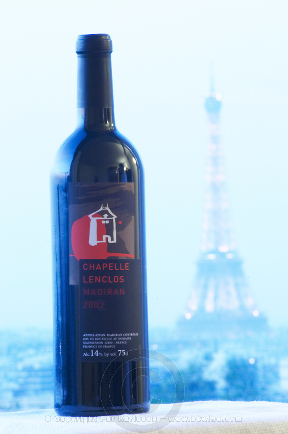 Bottle of Chapelle Lenclos against a pale blue background view over Paris with the Eiffel Tower Madiran France