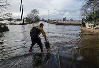 Flooding in the Somerset Levels, village of Burrowbridge. 8-2-14 Environment agency worker collects an oil can floating in the flood.