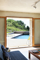 The outdoor swimming pool is framed in the open doorway of the bedroom