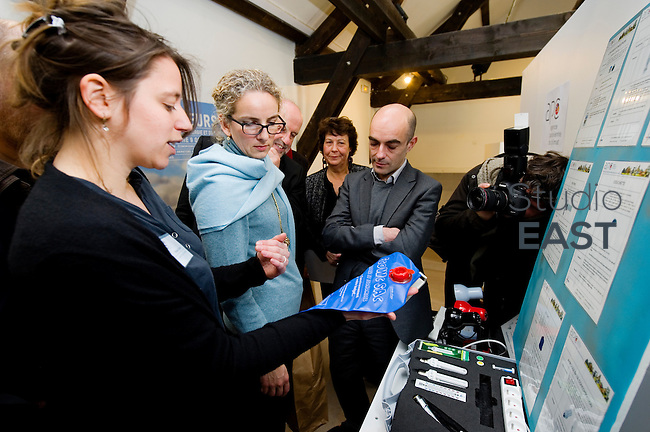 Mme Delphine Batho (centre, écharpe bleue), ministre de l'environnement et de l'énergie, écoute les conseils d'un conseiller qui lui présente un sac permettant de réduire la consommation de la chasse d'eau, à l'Agence Parisienne du Climat (ACP), dans le parc de Bercy, à Paris, France, le 30 mars 2013. Photo : Lucas Schifres
