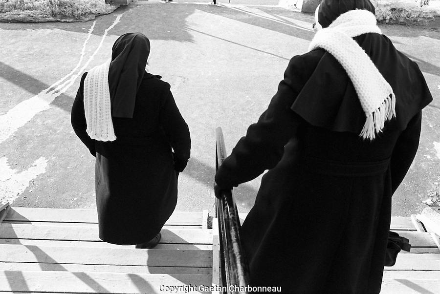Two sisters walking down the stairs, dressed in black winter coats