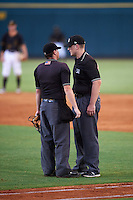 Umpires Jordan Johnson (left) and Dave Attridge (right) discuss a call during a game between the Fort Myers Miracle and Bradenton Marauders on August 3, 2016 at McKechnie Field in Bradenton, Florida.  Bradenton defeated Fort Myers 9-5.  (Mike Janes/Four Seam Images)