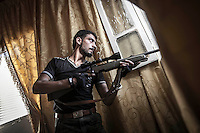 ABU AHEMD, the sniper of the Kateba Omar Ben Abdul Aziz sneak through a house buildings as he looks for the army troops to target them at the Aamria battlefield embedded inside a civilian neighborhood at the southwest of Aleppo City.  .