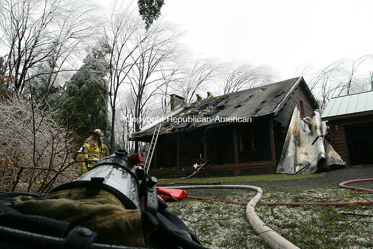 WINSTED, CT - 12 December, 2008 - 121208MO03 - Firefighters douse the last of the flames at 113 Highview Drive in Winsted Friday morning. A fire that started in or near a generator caused heavy damage to the home, but no injuries resulted. Jim Moore Republican-American.