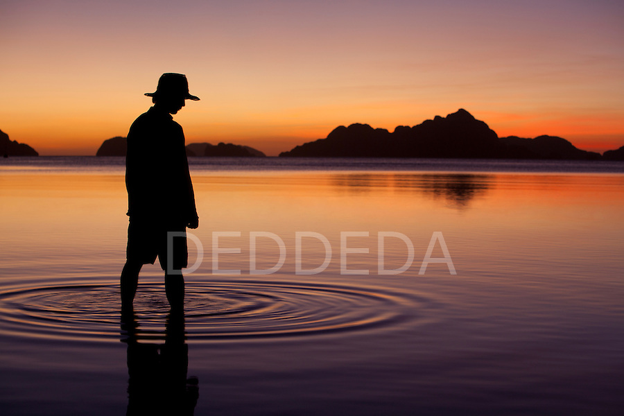 A man stands in tranquil water at Corong Corong, a seaside village near El Nido, in the famous and beautiful Bacuit Archipelago in Palawan, Philippines.