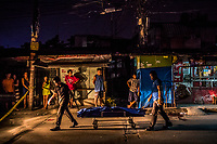 "MANILA, PHILIPPINES - OCTOBER 02: Funeral workers remove the body of Michael Araja, 29, an alleged drug user lays in front of ""sari sari"" a local convenience store, after being gunned down in the street by unidentied men in a ""riding-in-tandem"" killing in the early hours of October 02, 2016 in Manila, Philippines. According to neighbors, two unidentified men on a motorcycle, stopped as Mr Araja, had left his home to buy cigarettes and a drink for his wife, and gunned him down as he stood in front of his local convenience store. This type of murder perpetrated two peope on a motobike, is commonly referred to as a ""riding-in-tandem"" killing.  <br /> Photo by Daniel Berehulak for The New York Times"