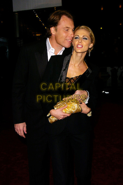 "DAMIEN ASPINALL & DONNA AIR.""Casino Royale"" World Royal Film Premiere Odeon cinema, Leicester Sqaure, London, UK..November 14th, 2006.Ref: CAN.half length gold clutch purse couple black suit funny face .www.capitalpictures.com.sales@capitalpictures.com.©Can Nguyen/Capital Pictures"