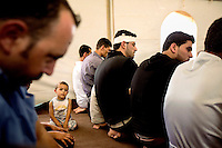 A small child sits among the men attending a tented mosque for Friday Prayers at Zaatari Refugee Camp. Approximately two million people have fled the conflict in Syria. At least 130,000 of them live in Zaatari Refugee Camp, although it was designed to house 60,000, and a further 2,000 people arrive each day.