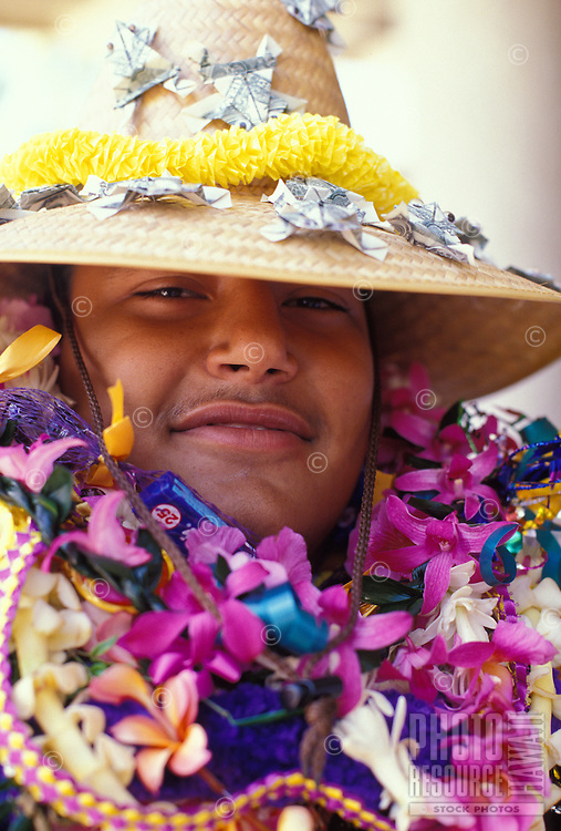Smiling young man covered with colorful leis at his high school graduation ceremory, Blaisdell Concert Hall, Honolulu