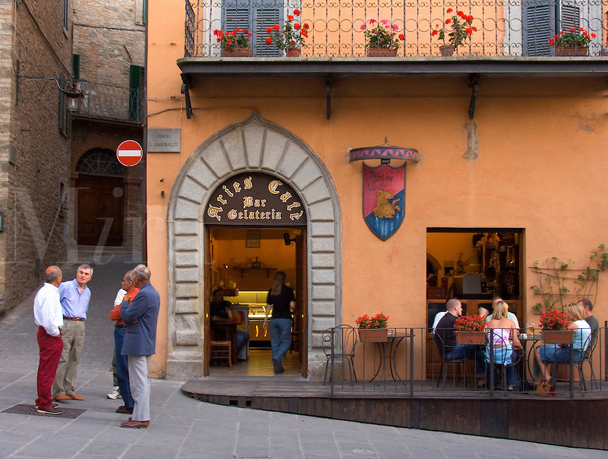 Men chat on corner and friends sit around table on outside deck of Aries Cafe Gelateria in the piazza Garibaldi in the Umbrian hilltown of Montone Ital