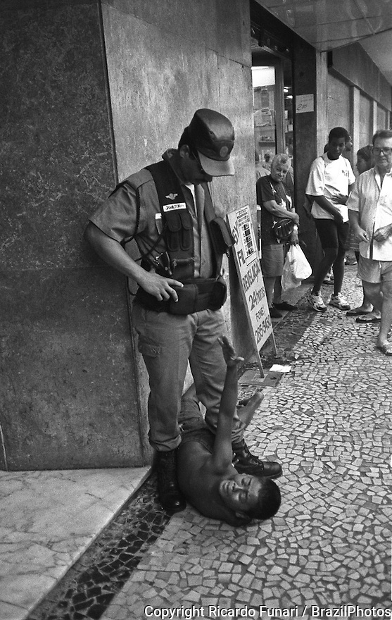 Rio de Janeiro, Brazil. Policeman arrests street child who has just tried to assault a pedestrian.