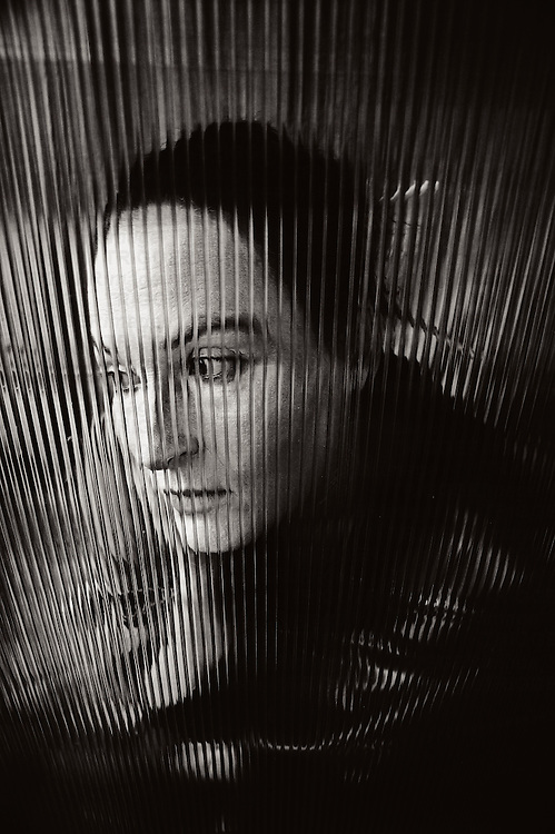 The face of a young woman behind corrugated glass looking to one size