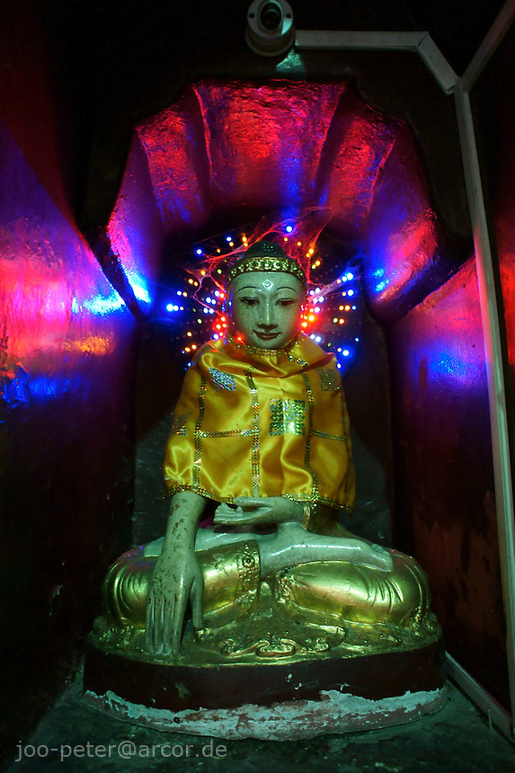 buddha sculpture in a shrine enlightened by color-changing electric lights,  Shwedagon pagoda complex, Yangon, Myanmar, 2011