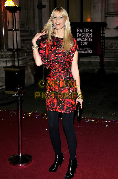 CLAUDIA SCHIFFER .attending the British Fashion Awards at Royal Courts of Justice, Strand,  London, England, UK, December 9th 2009..full length black and red print dress tights ankle boots pattern patterned peep toe clutch bag gold bracelet hand touching hair .CAP/PL .©Phil Loftus/Capital Pictures.