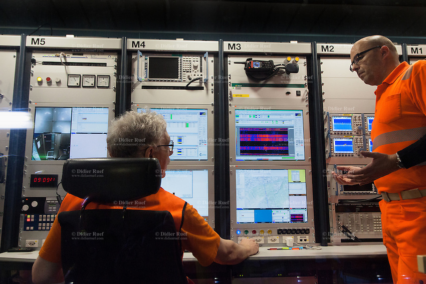 Switzerland. Canton of Grisons. Sedrun. Two technicians from the AlpTransit Gotthard Ltd talk together inside a SBB CFF FFS wagon used for various tests operations in the Gotthard Base Tunnel. Tests are being conducted of the interplay between the various processes, systems and equipment, which include the track, overhead conductor, power supply, tunnel infrastructure, train control and safety systems, as well as operational communications. The Gotthard Base Tunnel consists of two 57-kilometres-long single-track tubes, including all cross-passages, access tunnels and shafts. With a rock overburden of up to 2300 metres, the Gotthard Base Tunnel is not only the world's longest, but also the world's deepest, railway tunnel constructed to date. Two multifunction stations, at Faido and Sedrun, divide both tubes into three approximately equally long sections. The multifunction stations each contain emergency-stop stations and two track crossovers. The Gotthard Base Tunnel will be officially opened on June 1, 2016, and for scheduled commercial services in December 2016. The Gotthard Base Tunnel is a major technical implementation for a new railway line. With the New Rail Link through the Alps (NRLA), important goals of Swiss transport policy can be implemented: transfer of goods traffic from road to rail, and improvements with quicker travel in passenger trafic. 10.03.2016 © 2016 Didier Ruef