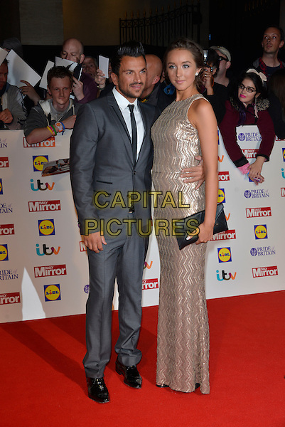 Peter Andre and Emily MacDonagh<br /> The Daily Mirror's Pride of Britain Awards arrivals at the Grosvenor House Hotel, London, England.<br /> 7th October 2013<br /> full length dress silver gold sleeveless grey gray suit pregnant couple black clutch bag<br /> CAP/PL<br /> &copy;Phil Loftus/Capital Pictures