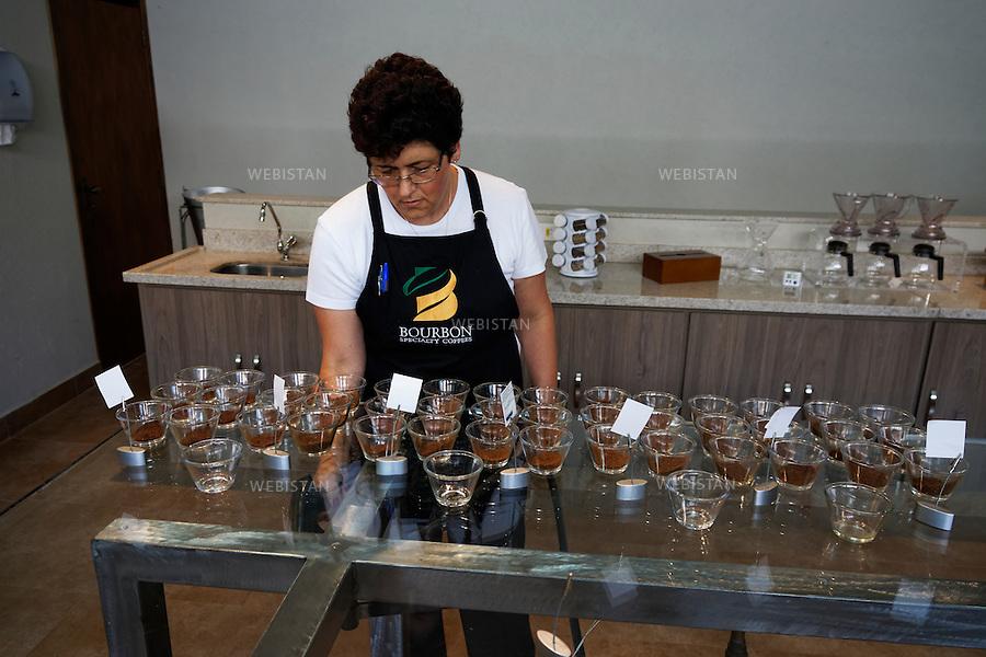Bresil, etat Minas Gerais, Pocos de Caldas, 1er novembre 2012.<br /> <br /> Societe Bourbon Speciality Coffee, negociant-exportateur de cafe, partenaire de Nespresso dans le cadre du programme AAA. Fondee en 2000, elle est reconnue dans tout le Bresil pour l'extreme qualite de ses grains et a recu de prestigieuses recompenses telles que &quot;Cup of Excellence&quot; et &quot;Late Harvest&quot;.<br /> Une employee prepare la table de tests en vue d'une analyse organoleptique. Dans chaque recipient, une qualite de cafe sur laquelle on verse de l'eau qui va reveler l'arome. Les differents cafes sont references sur une fiche technique.<br /> Reportage les Chants de cafe_soul of coffee, realise sur les acteurs terrain du programme de developpement durable Triple AAA de Nespresso.<br /> <br /> Brazil, Minas Gerais, Pocos de Caldas, November 1, 2012 <br /> <br /> The company, Bourbon Specialty Coffees, is a commercial exporter of coffee and a partner of Nespresso AAA program. Founded in 2000, the company is known throughout Brazil for the high quality of its coffee beans and it has received prestigious awards such as the &ldquo;Cup of Excellence&rdquo; and &ldquo;Late Harvest.&rdquo;<br /> An employee prepares the testing table for an organoleptic analysis. In each container there is high-quality coffee that releases its aromas when water is poured over it. The different coffees are referenced on a data sheet. <br /> Assignment: les Chants de cafe_ Soul of Coffee, implemented on the fields of Nespresso&rsquo;s AAA Sustainable Quality Program.