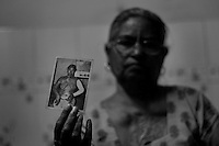 Sushil Kaur is showing her photograph taken in 1984. The mob which attacked her house and also set her ablaze had come in search of her husband whom they wanted to kill but couldn't get hold of. She suffered a 65% deep burn. Her husband who was absconding for 15 days got psychic seeing her condition and died few years later of cirrhosis of liver due to excessive consumption of alcohol. She presently stays with her son at Tilak Vihar. Tilak Vihar in New Delhi is called the widow colony. Widows and children of the Sikhs who were killed in 1984 Sikh Genocide live here. Four thousand Sikhs were killed in 72 hours in Delhi alone but no body till date has been punished for such an inhuman crime. Illiteracy, drug addiction, child labour and immense poverty characterize the area. Twenty five years ago all the male family members above the age of 15 were killed and burnt, leaving their uneducated widows and children behind to suffer, even after 25 years. The present generation is jobless, steeped in alcoholism and have lost their directions in life. November 2009. New Delhi, India, Arindam Mukherjee