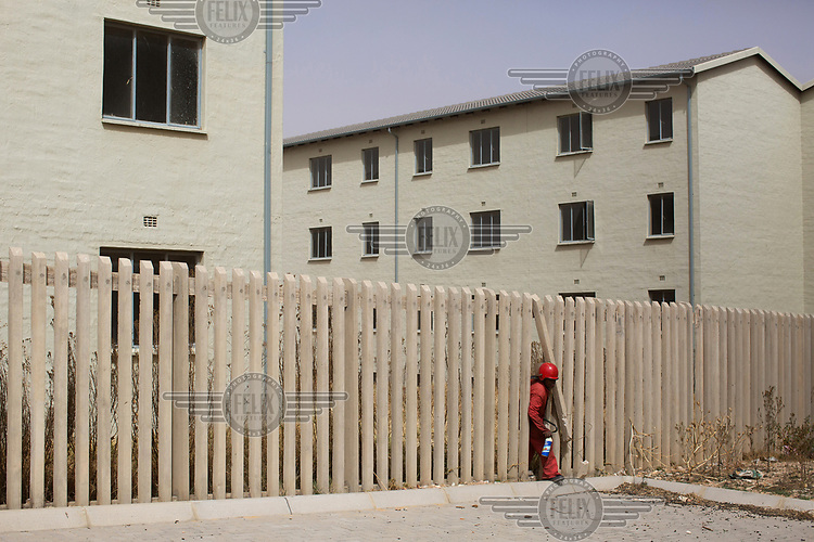 A Red ANt exits through the broken fence at an unoccupied government housing project in Fleurhof near Soweto. The project was completed more than 6 months previously and since then, the Red Ants have been guarding it against squatters. <br />The Red Ants are a controversial private security company often hired to clear squatters from land and so-called 'hijacked' properties.