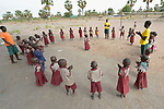 Students form a circle to sing in the Loreto Primary School in Rumbek, South Sudan. The Loreto Sisters began a secondary school for girls in 2008, with students from throughout the country, but soon after added a primary in response to local community demands.<br /> <br /> The two older girls leading the class are students of the Loreto Girls Secondary School. They took charge of the primary class so the regular teacher could attend a staff meeting.