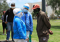 BOGOTA, COLOMBIA - April 14:  Government workers wearing a protective suite against Coronavirus talk to a homeless Venezuelan in Bogota, Colombia, Tuesday, April 14, 2020. Thousands of Venezuelan migrants were left on the streets of the main Colombian cities due to mandatory preventive quarantine decreed by the government to prevent the spread of the Covid-19 pandemic. (Photo by Daniel Munoz/VIEWpress)