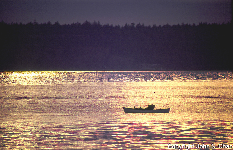 Silhouetted man lying supine in a rowboat, drifting on waters colored gold by sunset light. Alki Point, Seattle, Puget Sound, Washington.....Photographed in 35mm format on Velvia 50 film.