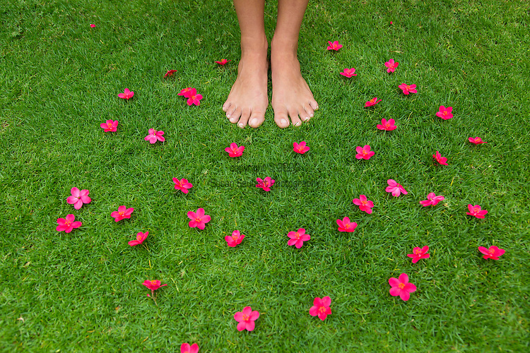 pink flowers with a happy face in the grass with bare feet, Maui, Hawaii, USA
