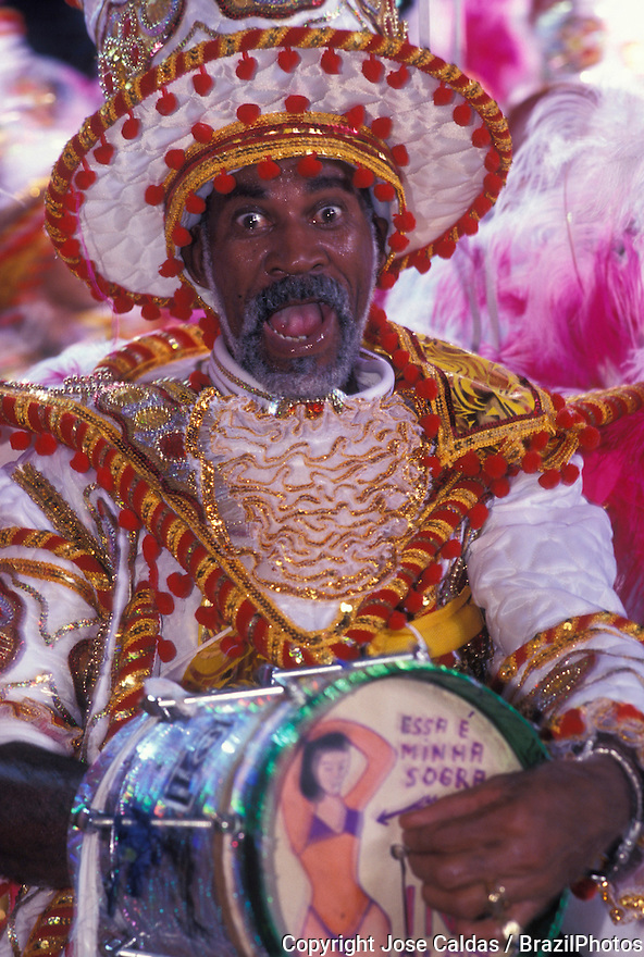 "Carnival, Samba Schools Parade, Rio de Janeiro, Brazil - drummer playing samba ( bateria ) wearing colorful costumes - Cuica, a percussion instrument open at one end and having a stick attached to the center of the drum-skin which, when rubbed, produces a grunting noise. ""Essa é minha sogra"" means ""This is my mother-in-law""."