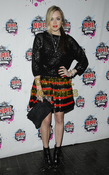 FEARNE COTTON.The Shockwaves NME Awards 2010 held at Brixton Academy, London, England. .February 24th, 2010.full length black sparkly top red striped stripes skirt clutch bag ankle boots hand on hip.CAP/CAN.©Can Nguyen/Capital Pictures.