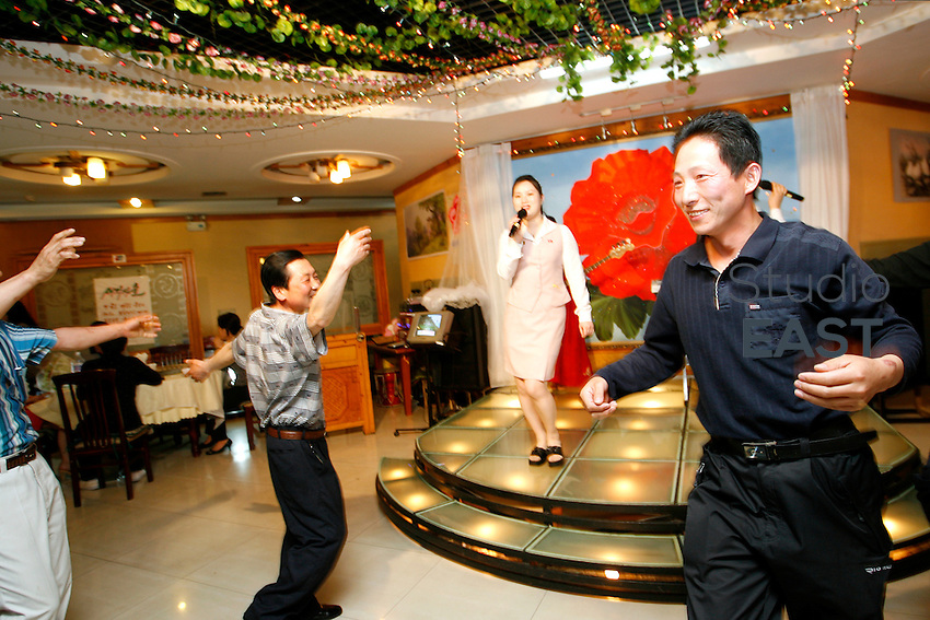 A North Korean waitress sings and entertains the audience at a North Korean restaurant, in Tonghua, Jilin province, China, on May 8, 2009. This restaurant is unique: it is the only North Korean restaurant with North Korean staff in China. The ten North Korean waitresses here are ones of the very few North Koreans, others than diplomats, allowed out of their country. All of them able to sing and dance, they come to China for an 3-year internship, missing very much their family left in North Korea. Photo by Lucas Schifres/Pictobank