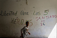 "A Cuban boy runs in front of the concrete wall with a propaganda writing in Abel Santamaría, a public housing suburb of Santiago de Cuba, Cuba, 31 July 2008. The Cuban economic transformation (after the revolution in 1959) has changed the housing status in Cuba from a consumer commodity into a social right. In 1970s, to overcome the serious housing shortage, the Cuban state took over the Soviet Union concept of social housing. Using prefabricated panel factories, donated to Cuba by Soviets, huge public housing complexes have risen in the outskirts of Cuban towns. Although these mass housing settlements provided habitation to many families, they often lack infrastructure, culture, shops, services and well-maintained public spaces. Many local residents have no feeling of belonging and inspite of living on a tropical island, they claim to be ""living in Siberia""."