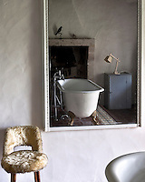 An antique free-standing bath is reflected in this simple mirror in the bathroom