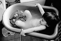 Switzerland. Canton Ticino. Lugano. Micaela Ruef is taking a bath. She enjoys the water and plays with two plastic toys, a dolphin and a parrot. MODEL RELEASED. © 1999 Didier Ruef