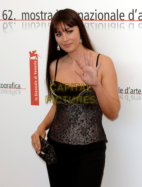 "MONICA BELLUCCI.photocall for ""The Bothers Grimm"".62nd International Film Festival,.Venice, 4th September 2005.half length La Biennale black corset strappy lace top skirt diamond dimante earrings clutch bag purse hand hip wave waving palm.Ref: PL.www.capitalpictures.com.sales@capitalpictures.com.©Capital Pictures."
