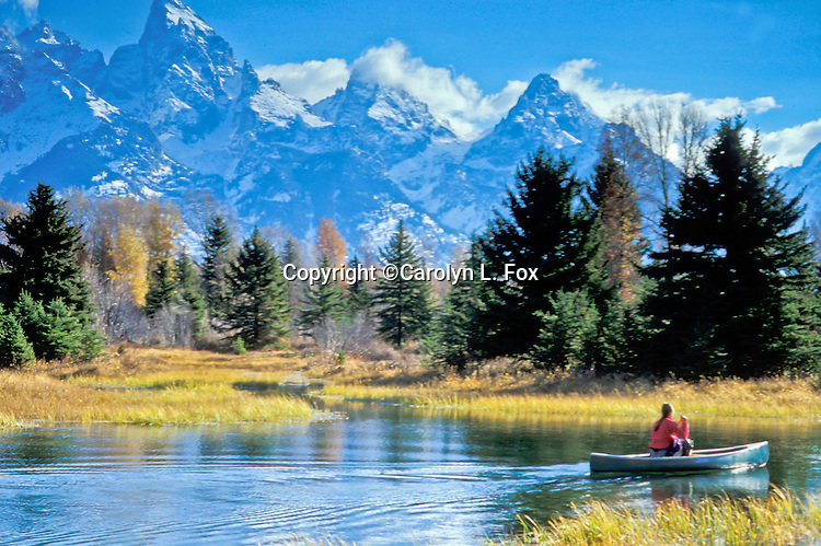 A woman paddles a canoe on the Snake River in Grand Teton National Park in Wyoming, USA.