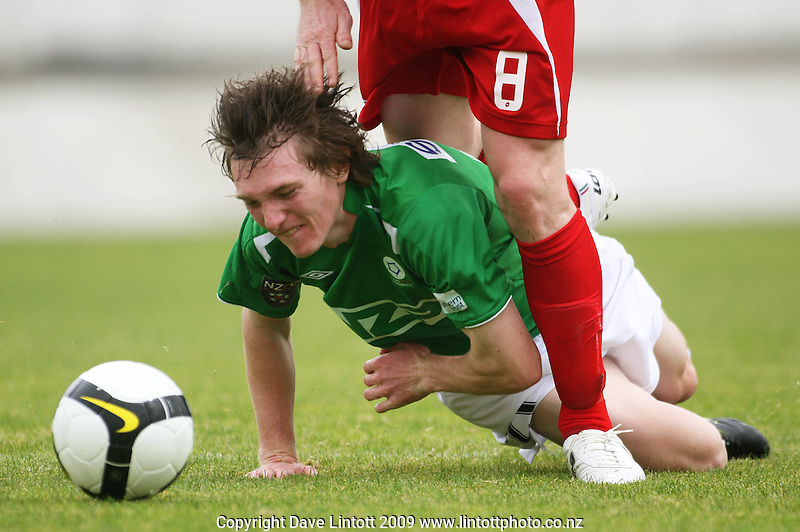 Manawatu's Corey Chettleburgh goes down under the challenge of Brent Fisher..NZFC Championship soccer - Youngheart Manawatu v Waitakere United at Memorial Park, Palmerston North. Sunday, 15 November 2009. Photo: Dave Lintott/lintottphoto.co.nz