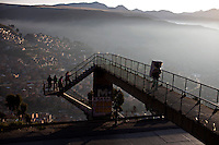 A man walks on top of a bridge early morning on the main highway from La Paz to El Alto.Just 25 years ago it was a small group of houses around La Paz  airport, at an altitude of 12,000 feet. Now El Alto city  has  nearly one million people, surpassing even the capital of Bolivia, and it is the city of Latin America that grew faster ...It is also a paradigmatic city of the tubles and traumas of the country. There got refugee thousands of miners that lost  their jobs in 90 ¥s after the privatization and closure of many mines. The peasants expelled by the lack of land or low prices for their production. Also many who did not want to live in regions where coca  growers and the Army  faced with violence...In short, anyone who did not have anything at all and was looking for a place to survive ended up in El Alto.