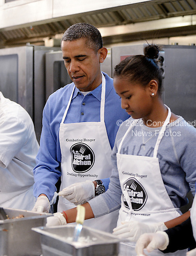 United States President Barack Obama and daughter Sasha participate in a community service project at the D.C. Central Kitchen in commemoration of the Martin Luther King, Jr. Day of Service and in honor of Dr. King's life and legacy on Monday, January 20, 2014 in Washington DC. <br /> Credit: Olivier Douliery / Pool via CNP