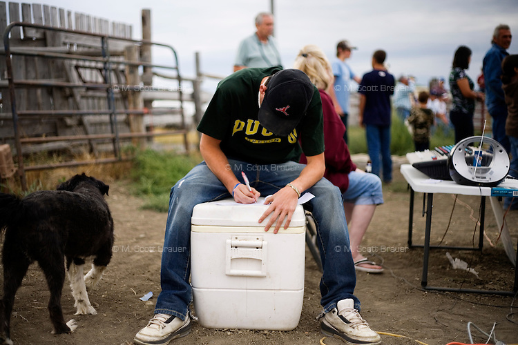 A teenager sits on a cooler filling out a 50-50 ticket at the Mechanical Bull-A-Rama at the Whoa Arena in Valier, Montana, USA.  The event, organized by Janelle Nelson, was a benefit for local youth rodeo participants and the local food bank.