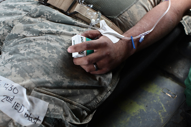 "A U.S. soldier wounded in a Taliban bomb explosion near Kandahar, Afghanistan, clutches a pack of cigarettes while being flown to a NATO military hospital by a helicopter ambulance with the 101st Combat Aviation Brigade's ""Shadow Dustoff."" Sept. 21, 2010. DREW BROWN/STARS AND STRIPES"