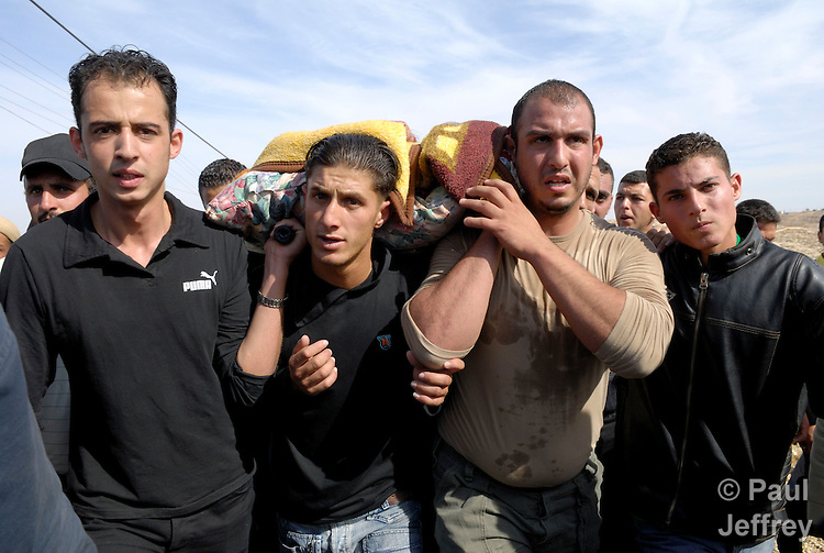 The body of Thear Hasan, a Palestinian killed by Israeli soldiers the night of November 3, 2006, is carried to a cemetery outside the West Bank city of Bethlehem by thousands of mourners the following day. Before killing Hasan, who they claimed was a militant, the Israelis destroyed an apartment building where Hasan reportedly lived.