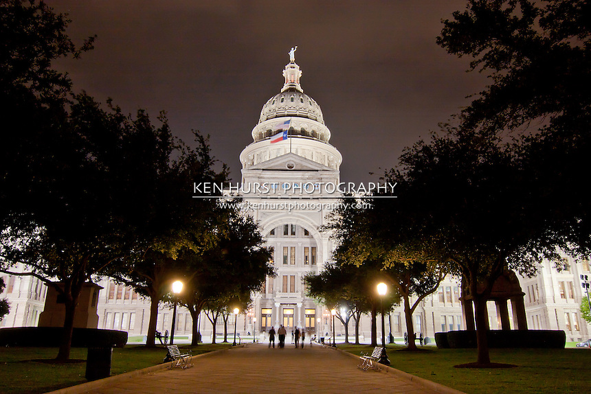 Texas Capitol building in Austin, Texas at night with visitors strolling in front of it.