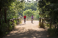 A man and woman chat and enjoy each others company while mountain biking on trails at the Zilker Park Hike And Bike Trail in Austin, Texas.