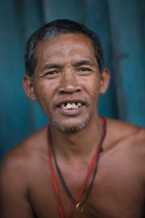 A man sits outside of his house in a squatter village in Manila.