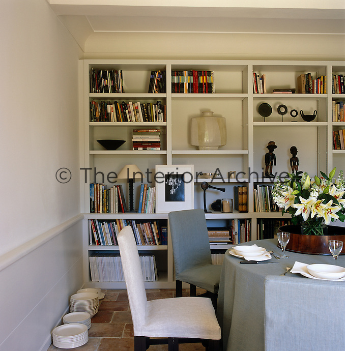 Floor-to-ceiling shelving in the dining room provides storage for books and displays objets d'art